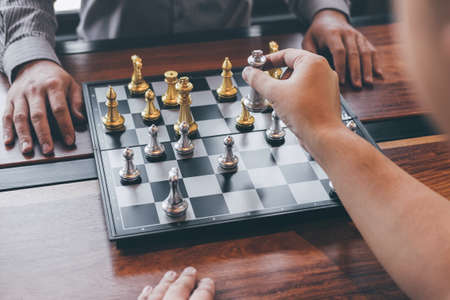 Intelligent businessman playing chess game competition with the opposite team, planning business strategic to development for win and success, Gold and silver chess with player.