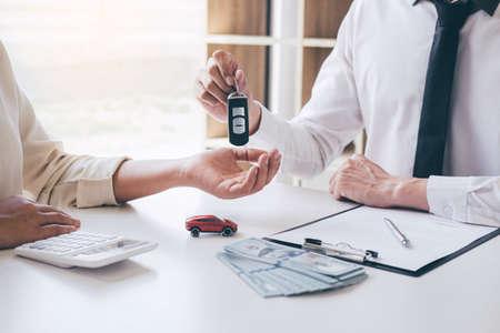 Manager van autoverhuuragent die sleutel van nieuwe auto vasthoudt die aan vrouwelijke klant geeft na ondertekening van een contract voor een goede dealovereenkomst, waarbij hij een voertuig huurt.