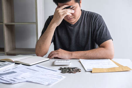Images of stressed Husband using calculator to calculating expenditure receipt bills of various activity cost and expenses in home office and written make report to plan of spent. Archivio Fotografico