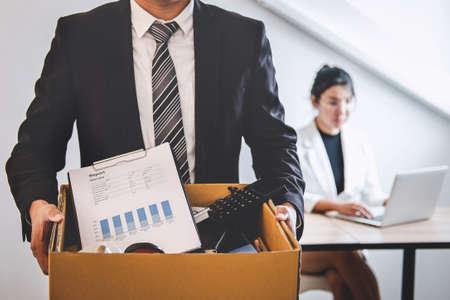 El hombre de negocios preparado enviará una carta de renuncia a la empresa y llevará sus pertenencias y archivos de embalaje en una caja de cartón marrón, cambiando y renunciando al concepto de trabajo.
