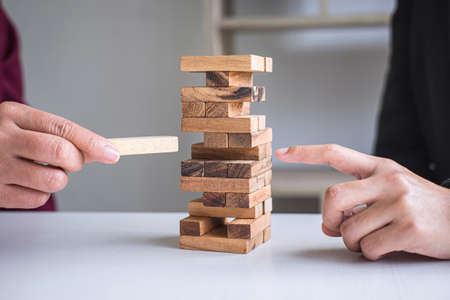 Risque et stratégie alternatifs dans les affaires, main de l'équipe d'affaires jeu coopératif en plaçant une hiérarchie de blocs de bois sur la tour pour une planification et un développement collaboratifs réussis.