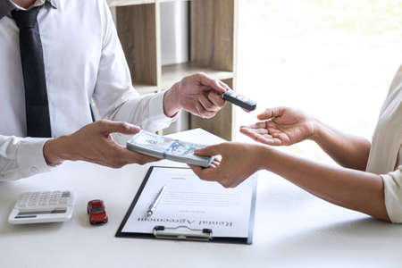Realtor agent manager holding key of new car giving to woman client after signing rental contract form and sending dollar us banknotes, renting considering vehicle car insurance.