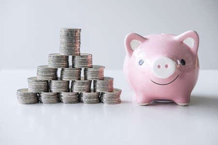Images of stacking coins pile and pink smiling piggy bank to growing and savings with money box, Saving money for future plan and retirement fund concept.