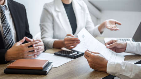 Employer or recruiter holding reading a resume with talking during about his profile of candidate, employer in suit is conducting a job interview, manager resource employment and recruitment concept. Stock fotó