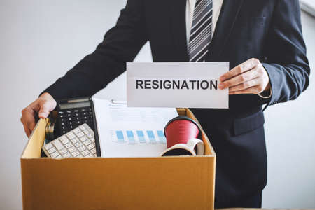 Businessman prepared will being sending resignation letter to company and carrying packing belongings and files into brown cardboard box, changing and resigning from work concept.