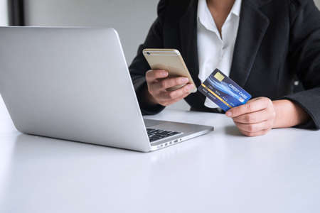Young woman consumer holding smartphone, credit card and typing on laptop for online shopping and payment make a purchase on the Internet, Online payment, networking and buy product technology. Foto de archivo - 128562914