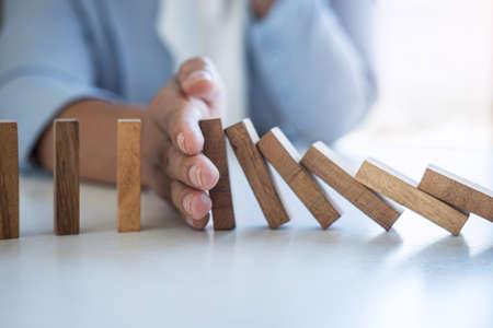 Rischio e strategia negli affari, immagine della mano che ferma la caduta dell'effetto domino del blocco di legno del crollo dal blocco rovesciato continuo, prevenzione e sviluppo alla stabilità.