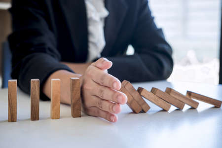 Risico en strategie in het bedrijfsleven, afbeelding van hand die stopt met vallende instorting houten blok dominostenen effect van continu omgevallen blok, preventie en ontwikkeling naar stabiliteit.