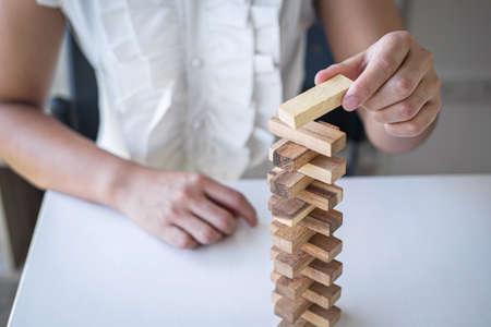 Alternative Risk and Strategy in Business, Hand of intelligent business woman gambling placing making wooden block hierarchy on the tower to planning and development to successful. Foto de archivo - 128562920