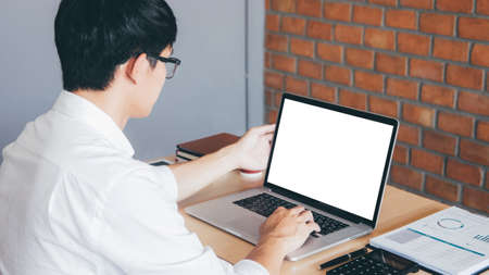 Image of Young man working in front of the laptop looking at screen with a clean white screen and blank space for text and hand typing information on keyboard in modern workspace. Foto de archivo - 128563925