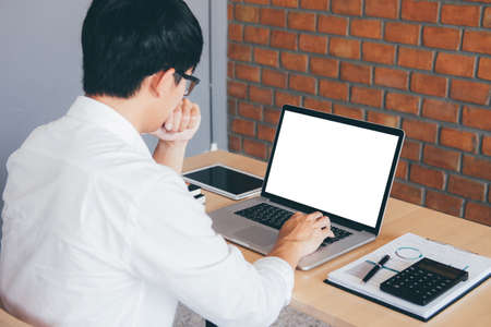 Image of Young man working in front of the laptop looking at screen with a clean white screen and blank space for text and hand typing information on keyboard in modern workspace. Foto de archivo - 128564055