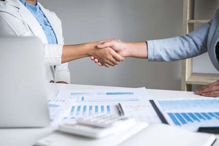 Finishing up a conversation after collaboration, handshake of two business woman leader after successful contract agreement to become a partner, collaborative negotiation partnership. Stock Photo