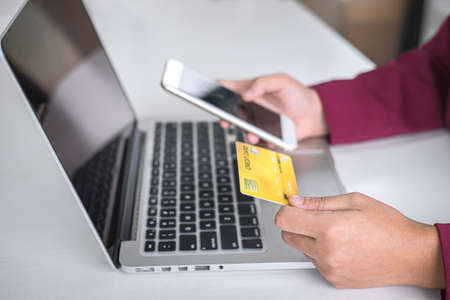 Young woman consumer holding smartphone, credit card and typing on laptop for online shopping and payment make a purchase on the Internet, Online payment, networking and buy product technology. Foto de archivo - 128564068