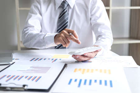 Businessman accountant working analyzing and calculating expense annual financial report balance sheet statement, doing finance making notes on report, Financing Accounting Banking Concept. Imagens