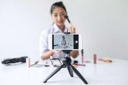 Business online sui social media, Beautiful Asian woman blogger sta mostrando il presente tutorial di prodotti cosmetici di bellezza e trasmette video in streaming live al social network mentre registra l'insegnamento online.