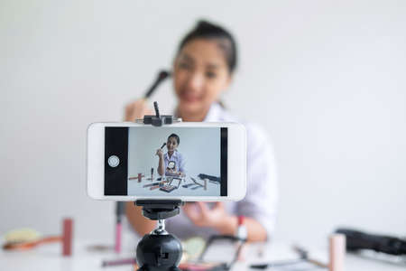 Business online on social media, Beautiful Asian woman blogger is showing present tutorial beauty cosmetic product and broadcast live streaming video to social network while recording teaching online.