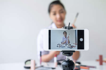 Business online on social media, Beautiful Asian woman blogger is showing present tutorial beauty cosmetic product and broadcast live streaming video to social network while recording teaching online. Foto de archivo - 128564310