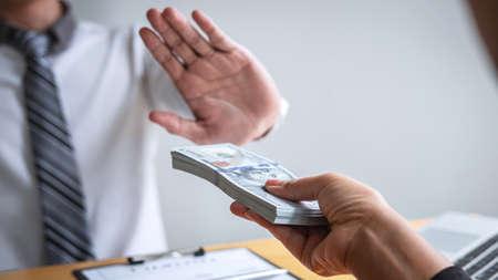 Concepto de lucha contra el soborno y la corrupción, el hombre de negocios se niega y no recibe billetes de dinero en la oferta de sobres de los empresarios para aceptar el contrato de acuerdo de inversión. Foto de archivo