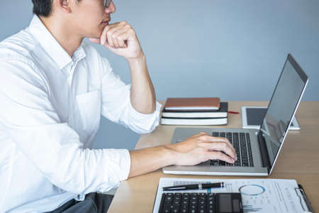 Image of Young man working in front of the laptop looking at screen with a clean white screen and blank space for text and hand typing information on keyboard in modern workspace. Foto de archivo - 128565967