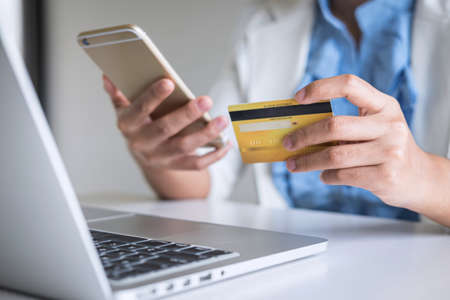 Young woman consumer holding smartphone, credit card and typing on laptop for online shopping and payment make a purchase on the Internet, Online payment, networking and buy product technology.