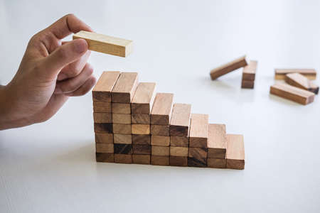 Alternative Risk and Strategy in business to make growth, Image of Business mans hand placing making a wooden block stacking hierarchy on growing to lay the foundation and development to successful.