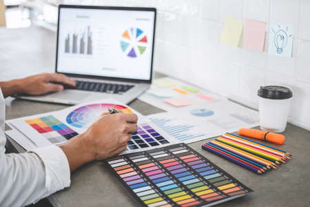 Young creative graphic designer working on project architectural drawing and color swatches, selection coloring on graphic chart with work tools and equipment. Imagens