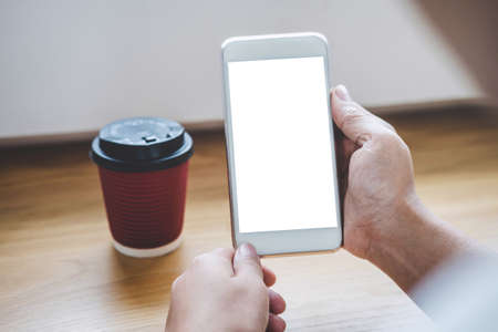 Image of Young woman looking at screen with a clean white screen and blank space for text, hand holding smartphone and typing with information and coffee cup in modern workspace. Imagens