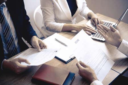 Empleador o comité que lee un currículum mientras habla sobre su perfil de candidato, el empleador en traje está realizando una entrevista de trabajo, el empleo de recursos del administrador y el concepto de contratación. Foto de archivo