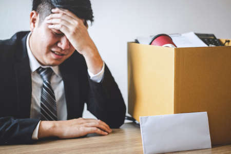 Stressed businessman receive fired letter from company and packing belongings and files into brown cardboard box, changing and resigning from work concept.