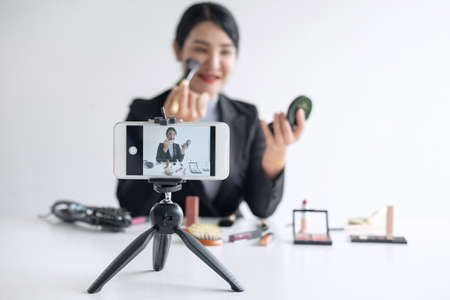 Business online on social media, Beautiful woman blogger is showing present tutorial beauty cosmetic product and broadcast live streaming video to social network while recording teaching online. Imagens