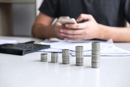 Images of stacking coin pile and Husband using smartphone to calculating expenditure receipt bills of various activity cost and expenses in home office and written make report to plan of spent.