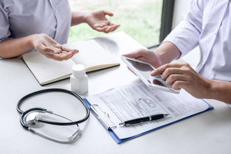 Doctor consulting with patient and checking sickness condition while presenting results diagnosis symptom examining about the problem of illness and recommend treatment method, Healthcare and medical. Imagens