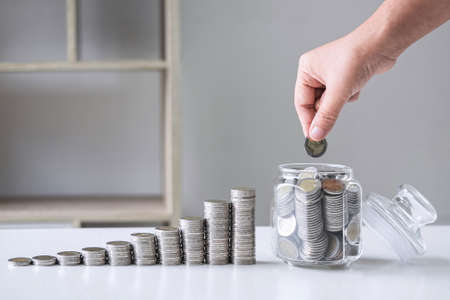 Images of growing stacking coins and Hand putting coin into glass bottle (money box) for planning step up and savings, Saving money for future plan and retirement fund concept.