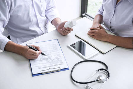 Doctor consulting with patient and checking sickness condition while presenting results diagnosis symptom examining about the problem of illness and recommend treatment method and using medicine. Фото со стока