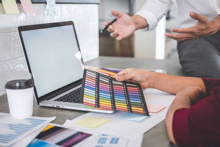 Teamwork of creative designers working on new project and choose color samples for selection coloring on digital graphic tablet with work tools and equipment at workplace.