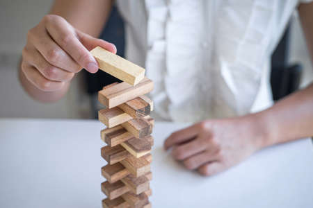 Alternative Risk and Strategy in Business, Hand of intelligent business woman gambling placing making wooden block hierarchy on the tower to planning and development to successful. Reklamní fotografie