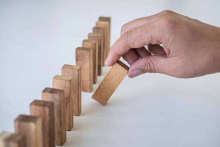 Risk and Strategy in Business, Image of hand gambling placing wooden block on a line of domino, prevention and development to stability.
