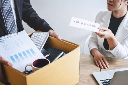 Stressed businessman receive fired letter from employer and packing belongings and files into brown cardboard box, changing and resigning from work concept. Stock Photo - 131733481