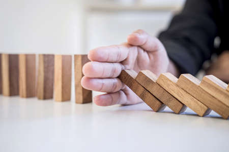 Risk and Strategy in Business, Image of hand stopping falling collapse wooden block dominoes effect from continuous toppled block, prevention and development to stability.
