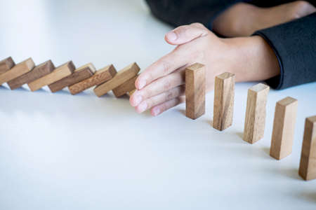 Risk and Strategy in Business, Image of hand stopping falling collapse wooden block dominoes effect from continuous toppled block, prevention and development to stability. Stock Photo - 131732930