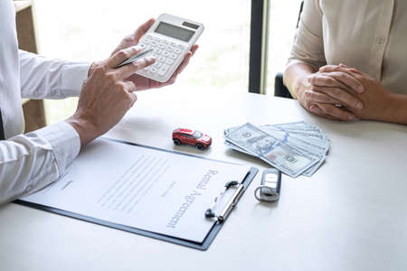 Realtor agent manager calculating and presenting to woman client for decide signing rental contract form, renting considering vehicle car insurance.