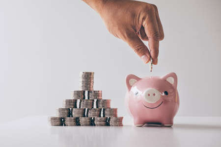Images of stacking coins pile and Hand putting coin into pink piggy bank for planning step up to growing and savings with money box, Saving money for future plan and retirement fund concept.