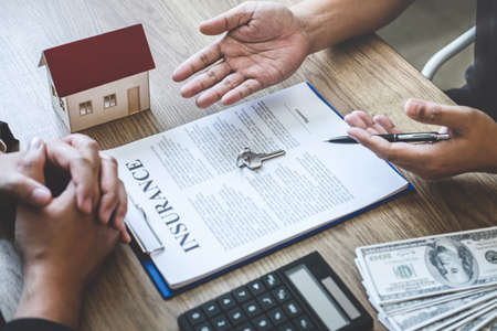 Estate agent broker reach contract form and presentation to client signing agreement contract real estate with approved mortgage application form, buying mortgage loan offer for and house insurance. Stock Photo - 132753760