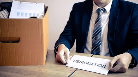 Stressed businessman will prepared being sending resignation letter to company and packing belongings and files into brown cardboard box, changing and resigning from work concept.