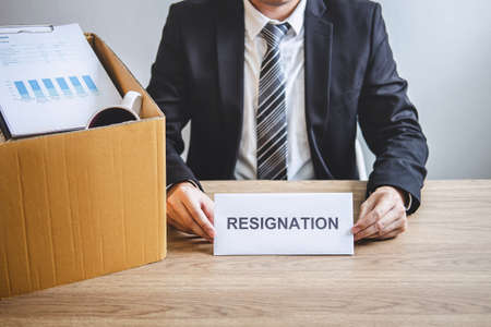 Stressed businessman will prepared being sending resignation letter to company and packing belongings and files into brown cardboard box, changing and resigning from work concept. Stock Photo - 131733501