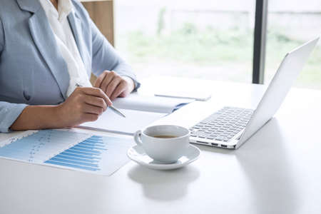 Business woman accountant financier working audit and calculating expense financial annual report balance sheet statement, doing finance checking document and making notes on report paper.
