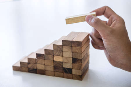 Alternative Risk and Strategy in business to make growth, Image of Business man's hand placing making a wooden block stacking hierarchy on growing to lay the foundation and development to successful. Stock Photo - 131733947