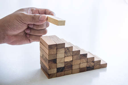 Alternative Risk and Strategy in business to make growth, Image of Business man's hand placing making a wooden block stacking hierarchy on growing to lay the foundation and development to successful.