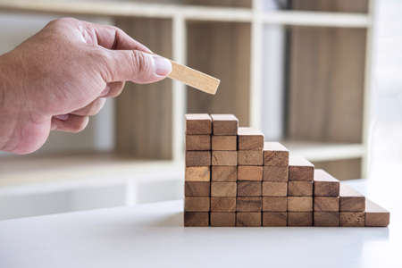 Alternative Risk and Strategy in business to make growth, Image of Business man's hand placing making a wooden block stacking hierarchy on growing to lay the foundation and development to successful. Stock Photo - 131733604