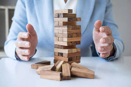 Alternative Risk and Strategy in business, Business womans hands protect balance wooden stack with hand control risk shape hierarchy on growing to lay the foundation and development to successful.